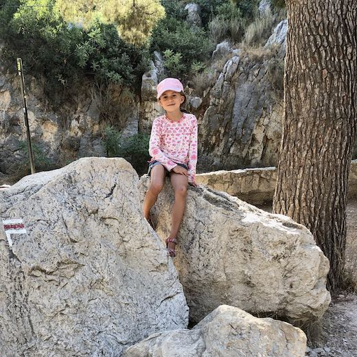 Little girl sitting on a rock near the Calanques de Cassis Provence