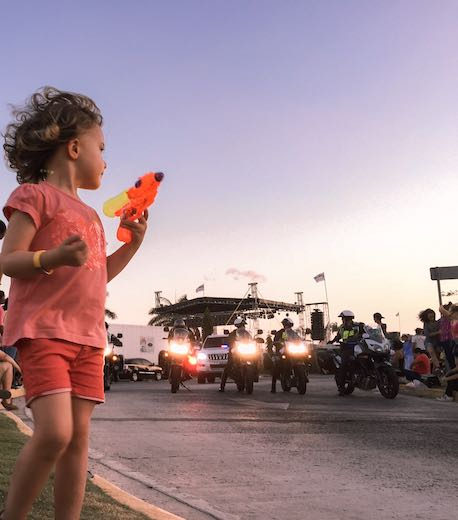 Little girl with brightly colored water pistol during carnival Panama
