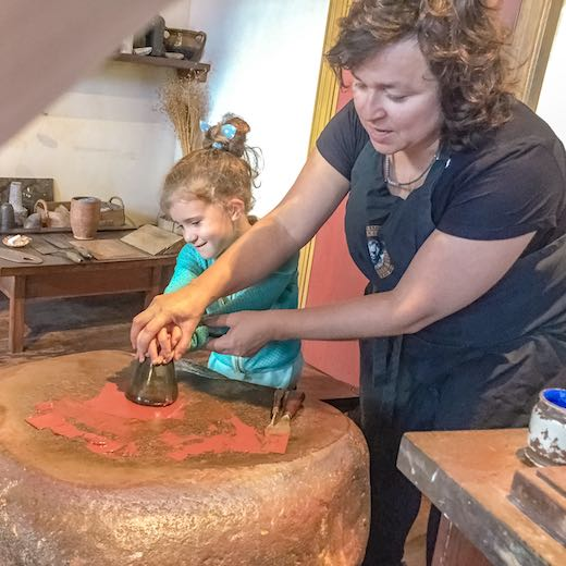 Little girl preparing the paint the Rembrandt way at the Rembrandt House Museum, one of the more unique things to do in Amsterdam