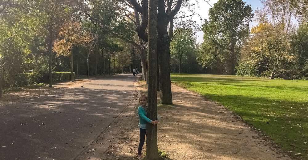 Little girl hugging a tree at Vondelpark in Amsterdam