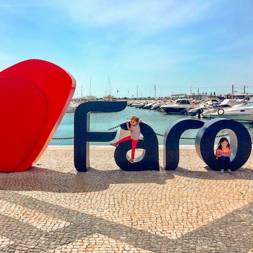 Little girls climbing on the letters of Faro Algarve