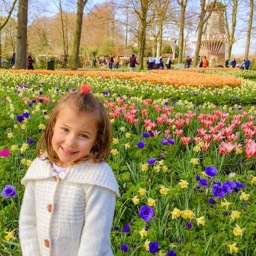 Little girl enjoying a visit to the flowers at the Keukenhof tulips Garden Holland