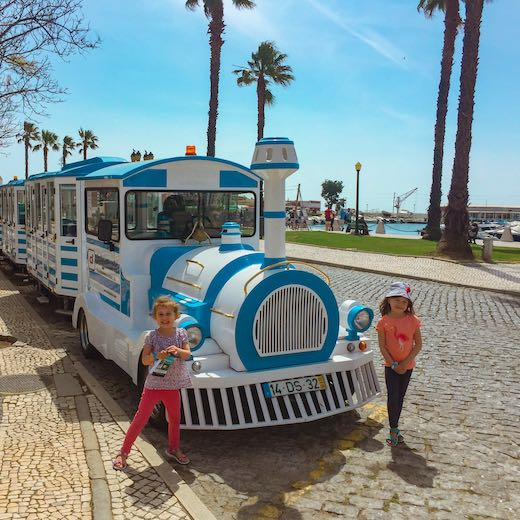 Two girls and a tourist train in Faro Portugal