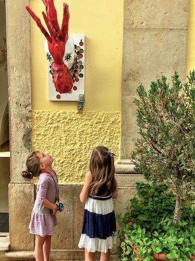 Two girls looking at the statue of a rooster in the streets of Loule, one of the best places to visit in Faro Algarve
