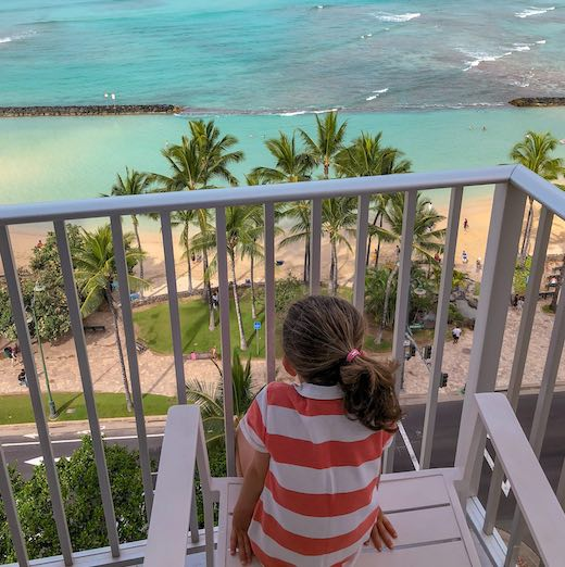 Girl on a chair at the hotel balcony watching flights from Honolulu to Maui