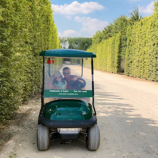 Father and daughter exploring the Gardens of Versailles in a golf cart