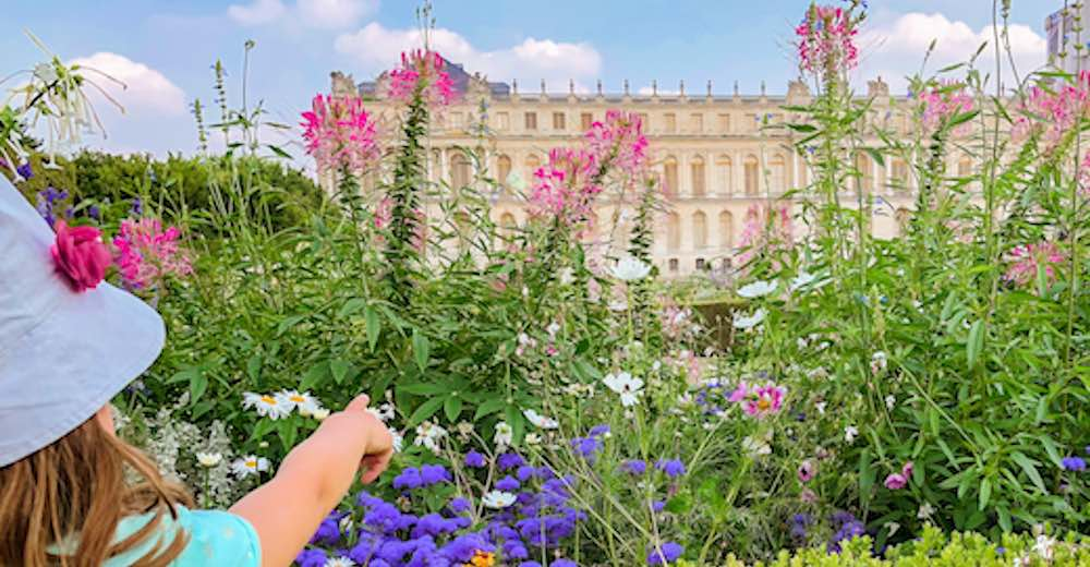 Little girl visiting Versailles and pointing to the Palace of Versailles from between the flowers