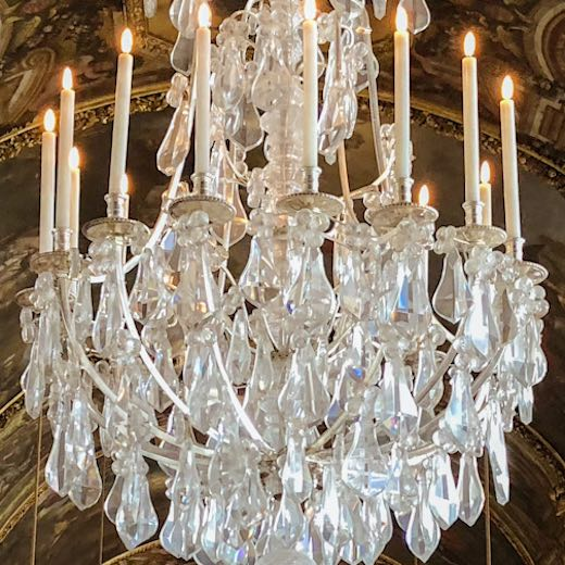 Take in the details of the Hall of Mirrors, like these chandeliers, during your Versailles Chateau visit