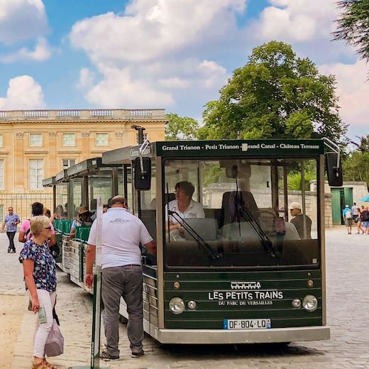 Tourist train to Versailles Trianon Palaces from the main Chateau and the Gardens
