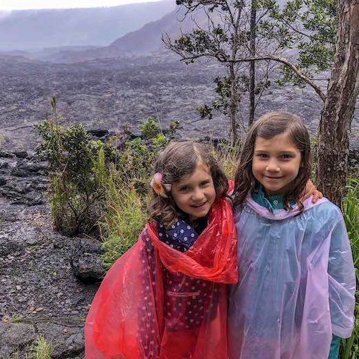 Two little girls at the Kilauea volcano with a poncho to protect from rainfall