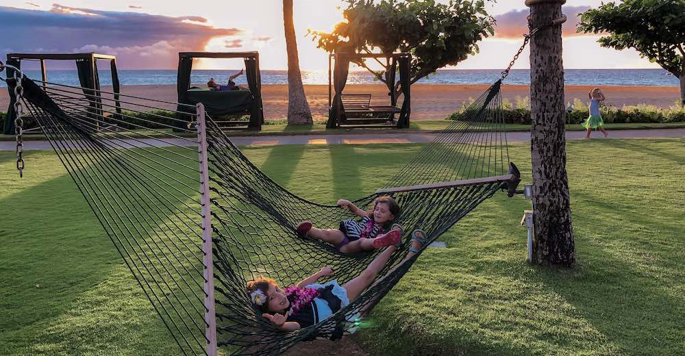 Two girl lounging in a hammock at Ka'anapali beach in Maui