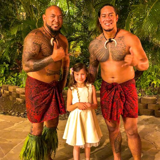 A girl having her picture taken with two Maui luau dancers