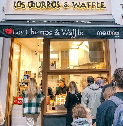 People buying waffles in Brussels at the Los Churros and Waffle counter