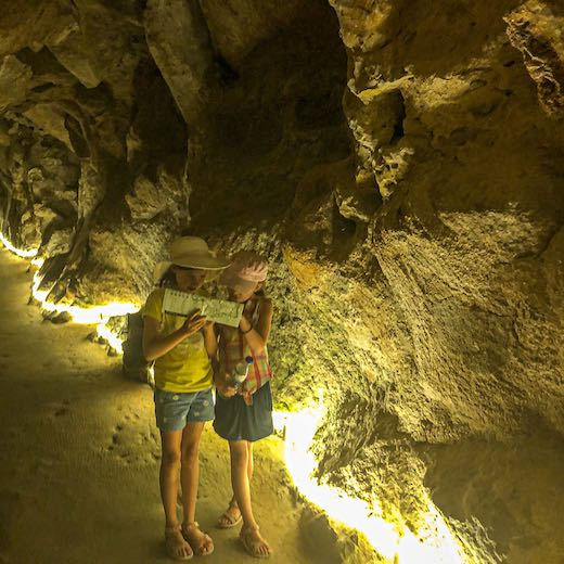 Two girls looking at the map in one of the Quinta da Regaleira caves