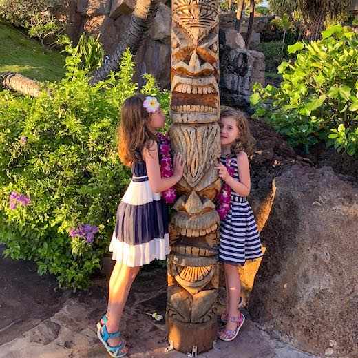 Two girls around a tiki statue at Ka anapali beach Maui