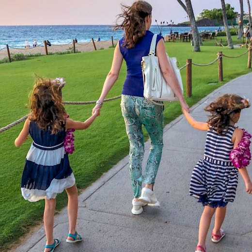 Mother and daughters hand in hand on the Kaanapali Beach Walk near Black Rock in Maui