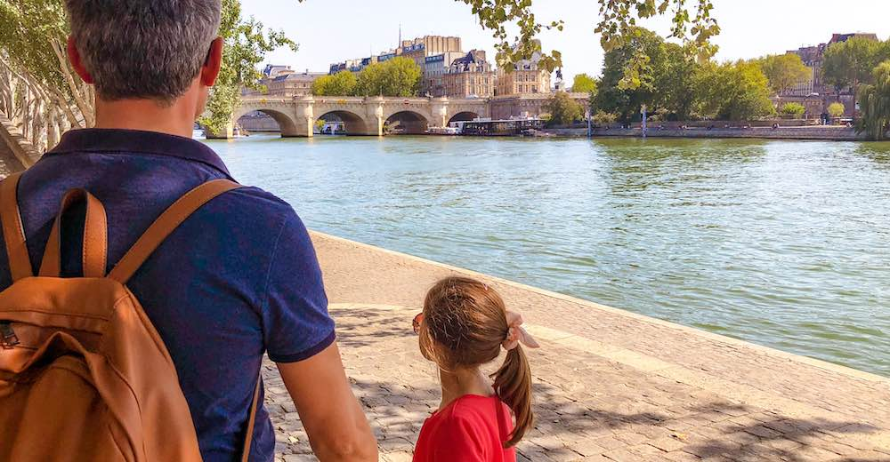 Father and daughter strolling along the Seine river during their visit to Paris