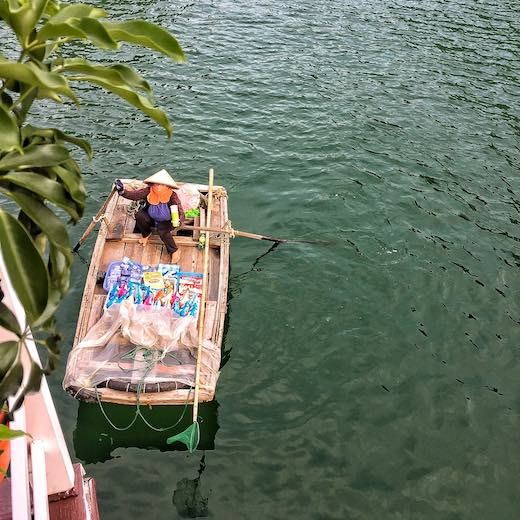 Vietnamese vendor on a bamboo boat at Halong Bay