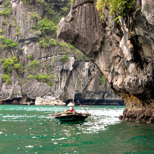 Local Vietnamese vendor on a bamboo boat at Halong Bay