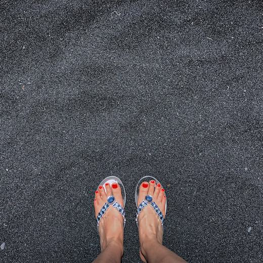 Flip flops, like the ones on this black sand beach, are a must on every beach vacation pack list