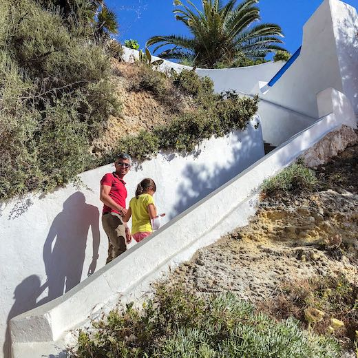 Father and daughter climbing the staircase next to Carvoeiro beach Portugal