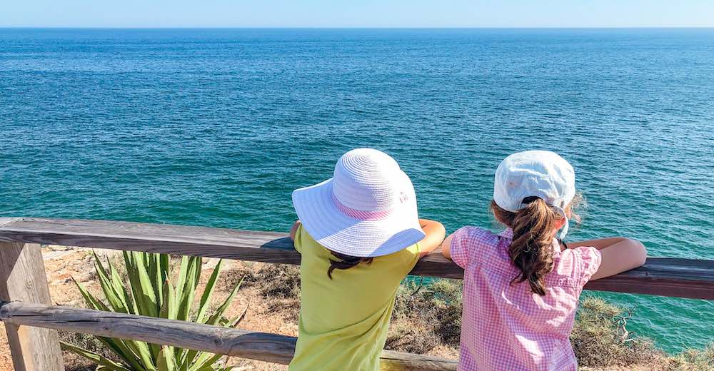 Two little girls overlooking the Atlantic from the Algarve Carvoeiro Boardwalk to Algar Seco