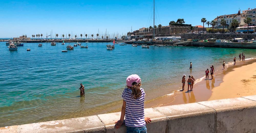 Little girl looking out over Praia da Ribeira, the most popular Cascais beach Portugal