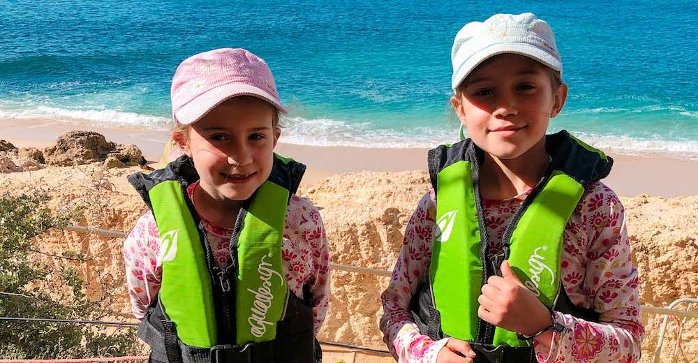 Two girls wearing safety vests and a hat, ready to kayak to Benagil Algarve Portugal beach cave