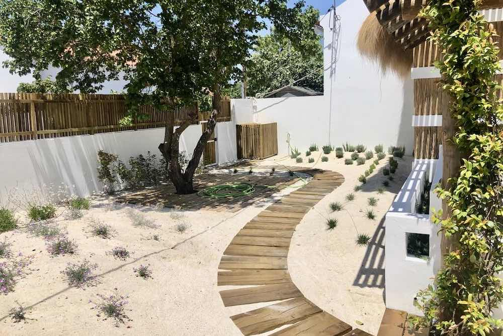 Winding wooden pathway in the sandy garden of a holiday accommodation Portugal