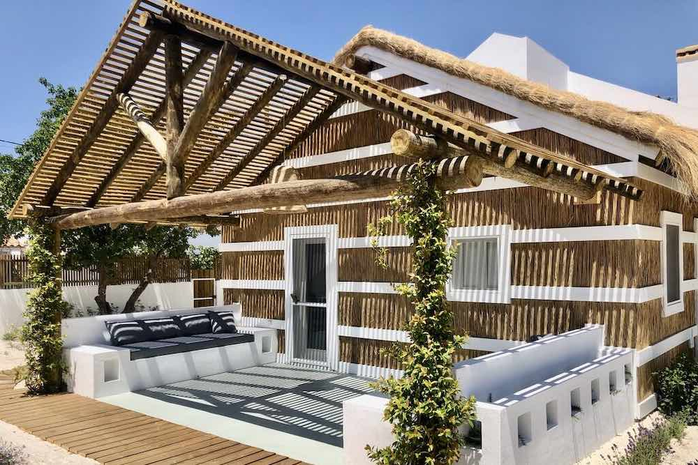 This beach cabin with thatched roof is one of the most enchanting renting villas in Portugal