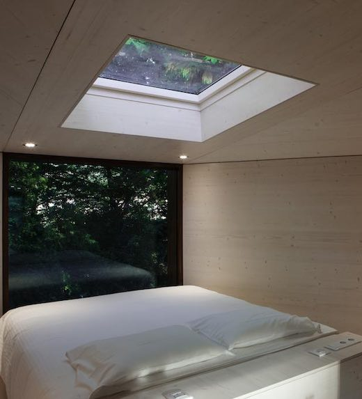 Bed with white sheets under a skylight and in front of a window for maximal forest view