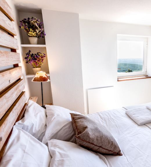 White and wooden decor of a bedroom of this Portugal rental house near Guincho beach