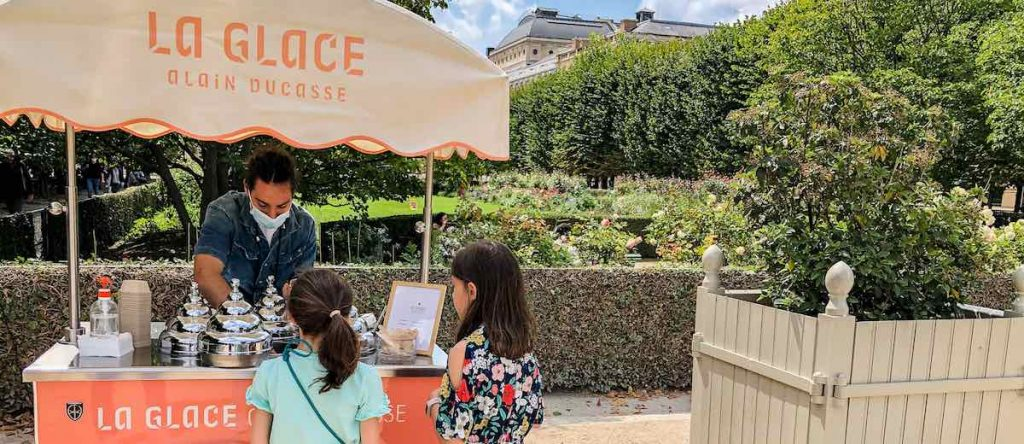 Two girls ordering an ice cream from a small food truck at the Jardin du Palais Royal Paris