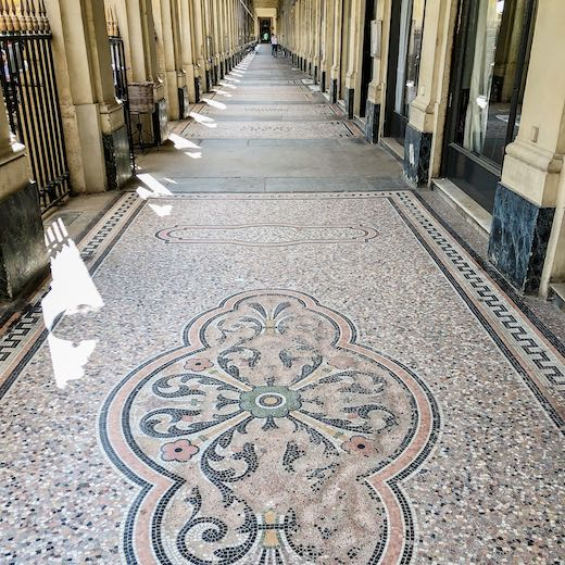 Arched galeries with mosaic floors frame the Palais Royal Paris