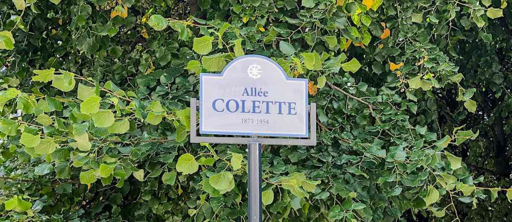 Name sign of the Allée Colette against a backdrop of verdant foliage